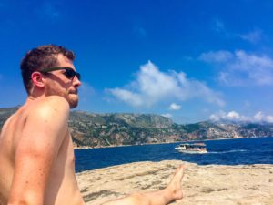 Jackson sitting naked as a tourist boat passes